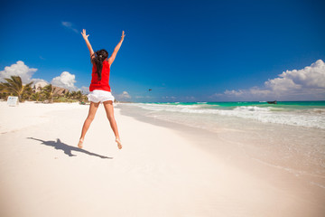 Young beautiful woman raises her arms up on the beach