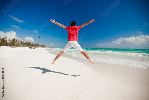 Young man jumping and raising his arms up on the beach