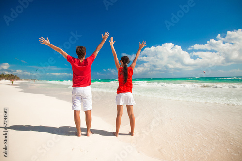 Back view of young couple spread their arms standing on white