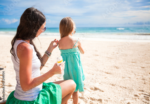 Mother protects her baby from the sun with suncream