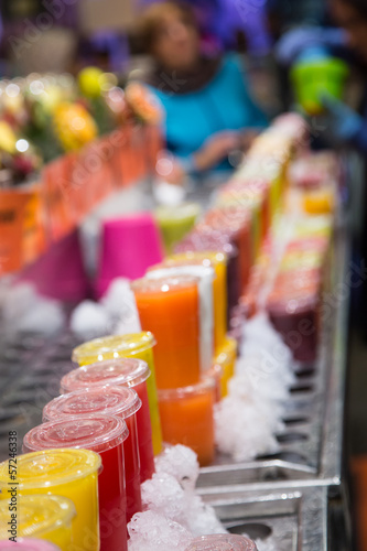 Plastic Cups of Colorful Fruit Juices in a Market