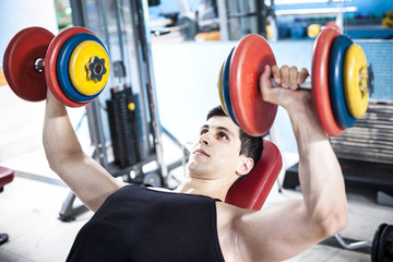 Strong man training with weights in the gym