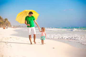 Young father and his little daughter walking under a yellow