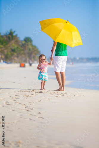 Back view of Young father and his little daughter walking under