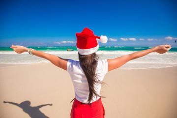 Back view of beautiful girl in Santa Hat walking spread her