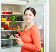 Young woman near fridge