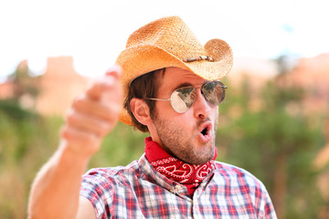 Cowboy man with sunglasses and hat pointing