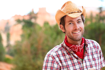 Cowboy man smiling happy wearing hat in country