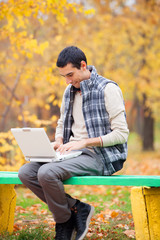 Programmer with notebook sitting in autumn park