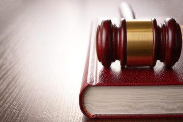 Wooden judges gavel lying on a law book in a courtroom for