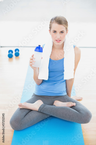 Peaceful pretty blonde in lotus position holding flask