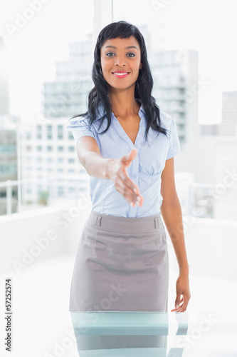 Pleased businesswoman presenting her hand