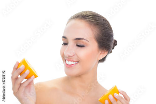 Amused young brunette woman looking at an orange half