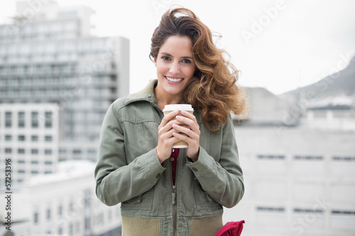 Smiling gorgeous brunette in winter fashion holding disposable c