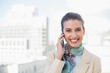 Pleased smart brown haired businesswoman making a phone call