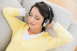 Relaxed casual brunette in yellow cardigan listening to music wi