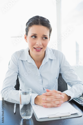 Skeptical stylish brunette businesswoman joining her hands and l