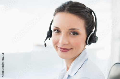 Content stylish brunette operator smiling and looking at camera
