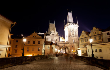 Tourists near Charles bridge in Prague at night.