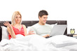 Disappointed girl in bed with her boyfriend working on a laptop