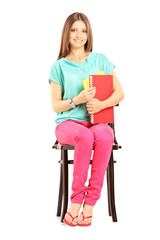 Smiling female student on a chair holding books