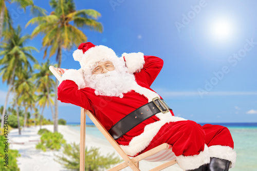 Relaxed Santa Claus sitting on a chair, on a beach, enjoying