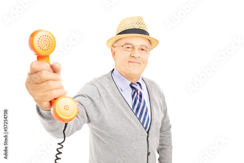 Senior gentleman giving a telephone to somebody to talk