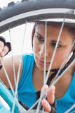 Athletic woman adjusting her spokes on bike wheel