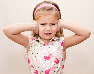 Little girl covering her ears