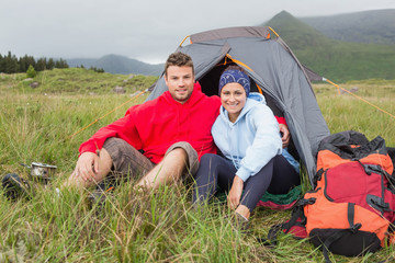 Couple on camping trip smiling at camera