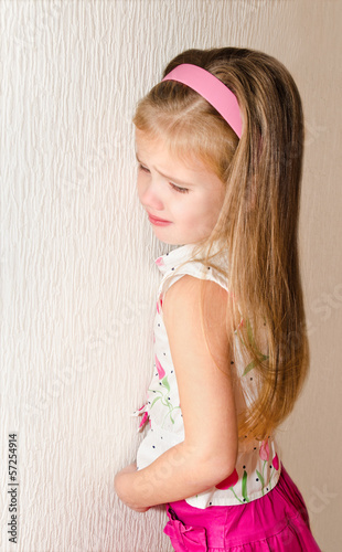 Naughty little girl is standing in the corner