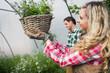 Beautiful woman touching a hanging flower basket