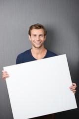 lächelnder junger mann zeigt weißes plakat