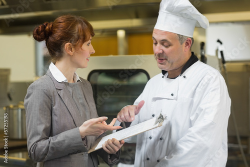 Young female manager talking to the head cook Poster