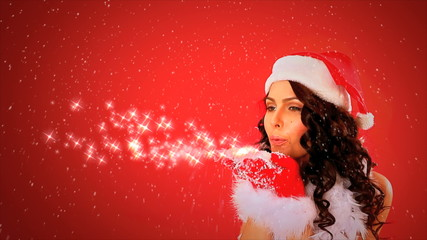 Woman in Santa hat blowing Xmas snowflake