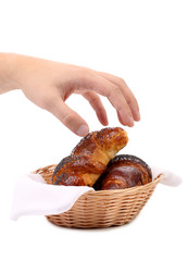 Croissants in a basket with hand.