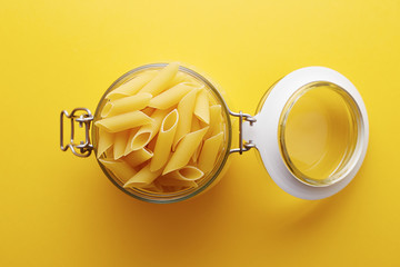 Raw pennoni rigati pasta on a glass jar