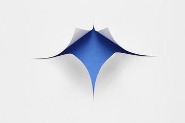 Blauer Hintergrund hinter zerschnittenem Papier