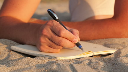 Man writing in his diary at the beach
