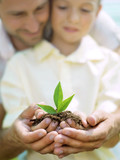 Father educate son to care a little plant