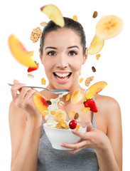 Beautiful young woman eating cereals and fruit