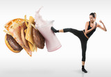 Fototapety Fit young woman fighting off fast food