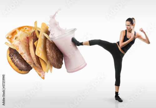Fit young woman fighting off fast food - 57259941