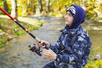 Boy fishing near river in autumn