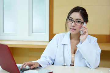 Young doctor woman speaking by phone mobile in her office