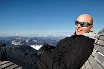 Mann liegt gemütlich am Berg in einer Liege