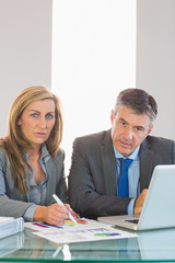 Two focused business people looking at camera trying to understa