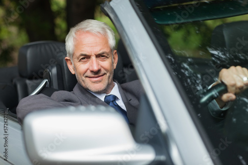 Content businessman driving expensive cabriolet