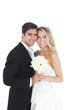 Sweet married couple posing holding a white bouquet