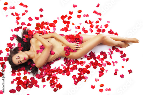 Foto op Aluminium Akt slim woman lying on red roses petals over white